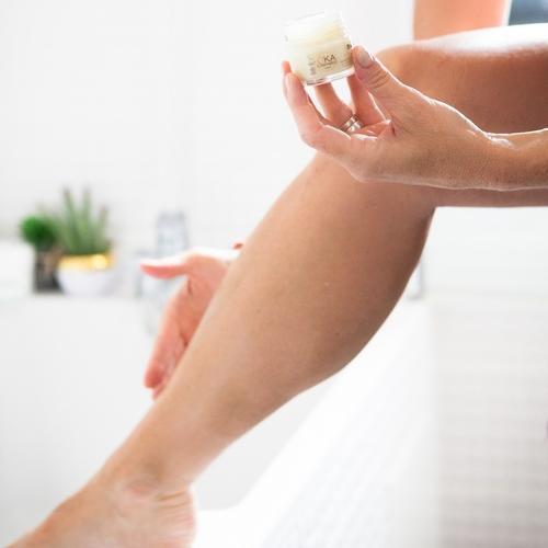 Femme qui se crème les jambes avec du beurre de karité