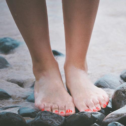 Pieds avec ongles vernis sur une plage de galets et sable